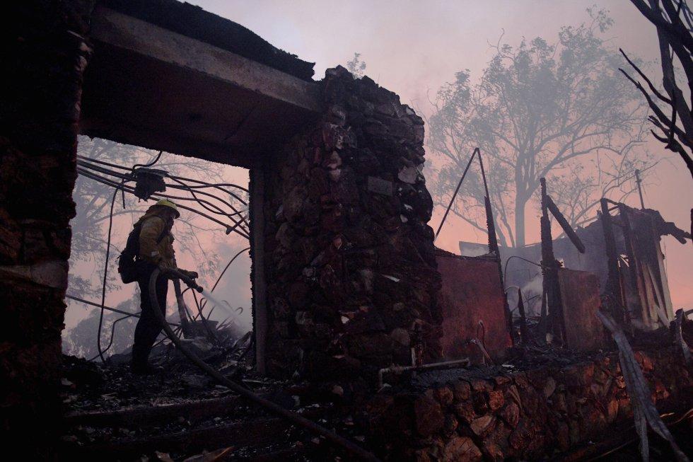 Un bombero utiliza la manguera en una casa humeante destruida por el incendio en Los Ángeles. rn