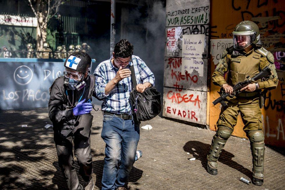 Leonardo, otro de los brigadistas voluntarios, ayuda a un hombre afectado por los gases lacrimógenos junto al carabinero que acaba de disparar.