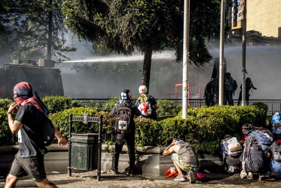 Nicolás y Leonardo se preparan para auxiliar a manifestantes mientras el camión lanza agua y un grupo se protege. Muchos voluntarios se coordinaron en grupos alrededor de varios vecindarios para tener lugares seguros donde brindar atención y resguardar a los heridos, además de conseguir los insumos médicos.