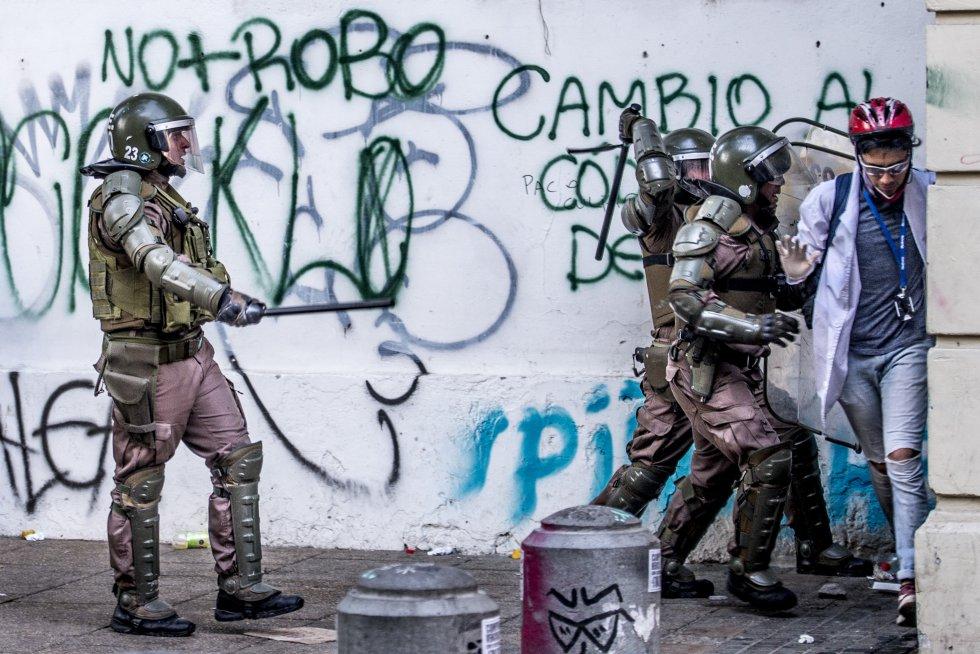 Un grupo de carabineros ataca con bastones al personal voluntario de primeros auxilios.
