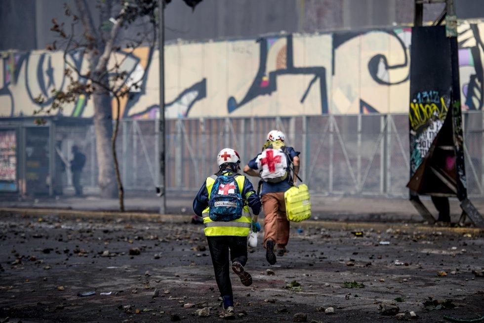 Dos voluntarios corren para protegerse en medio de una protesta en Santiago.