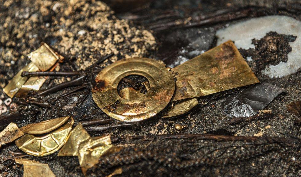 Imagen de piezas de oro halladas en la ofrenda de las dos aves de presa en el Templo Mayor. Se ve lo que parece un cetro o lanza y un escudo.
