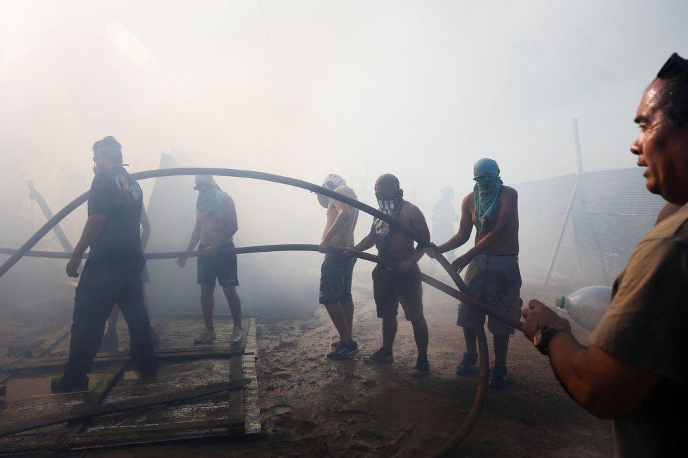 """""""Se han afectado más de 100 viviendas (...) es una situación muy difícil en una noche muy especial"""", ha declarado Gonzalo Blumel, ministro del Interior en una rueda de prensa el martes por la noche en la Oficina Nacional de Emergencia (Onemi) en Santiago. En la imagen, un grupo de vecinos intentan sofocar el incendio."""