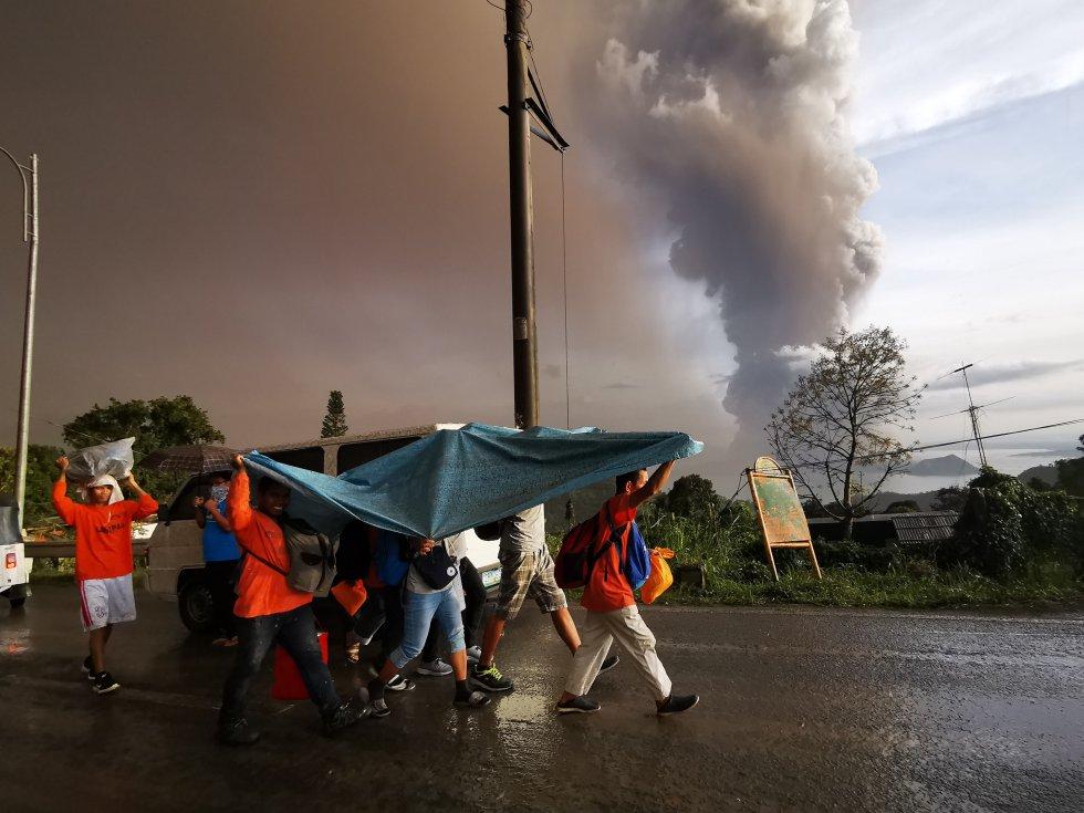Varios ciudadanos se cubren con una manta mientras evacuan la ciudad de Tagaytay. Al fondo, la columna de humo del volcán Taal.