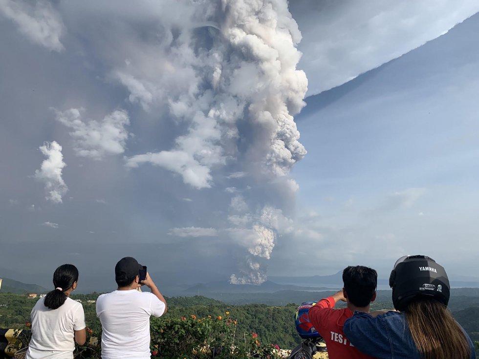 Miles de turistas visitan cada año el Taal y algunos realizan excursiones hasta su cráter, parcialmente inundado y en el que es fácil ver pequeñas fumarolas. En la imagen, varias personas fotografían la columna de ceniza del volcán Taal, desde Tagaytay.