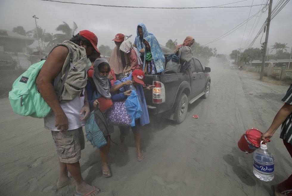 Una familia evacua a terrenos más seguros mientras el volcán Taal continúa arrojando cenizas en Lemery, Batangas (Filipinas), el lunes 13 de enero.