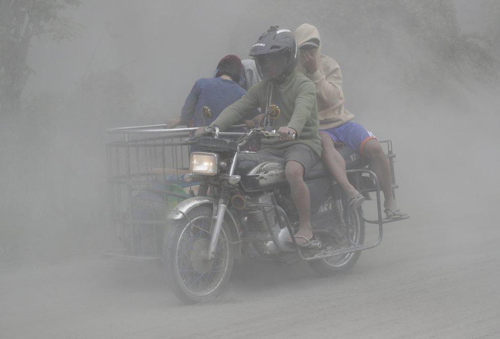 Una conduce su motocicleta a través de nubes de cenizas mientras evacúan a terrenos más seguros, el lunes 13 de enero.