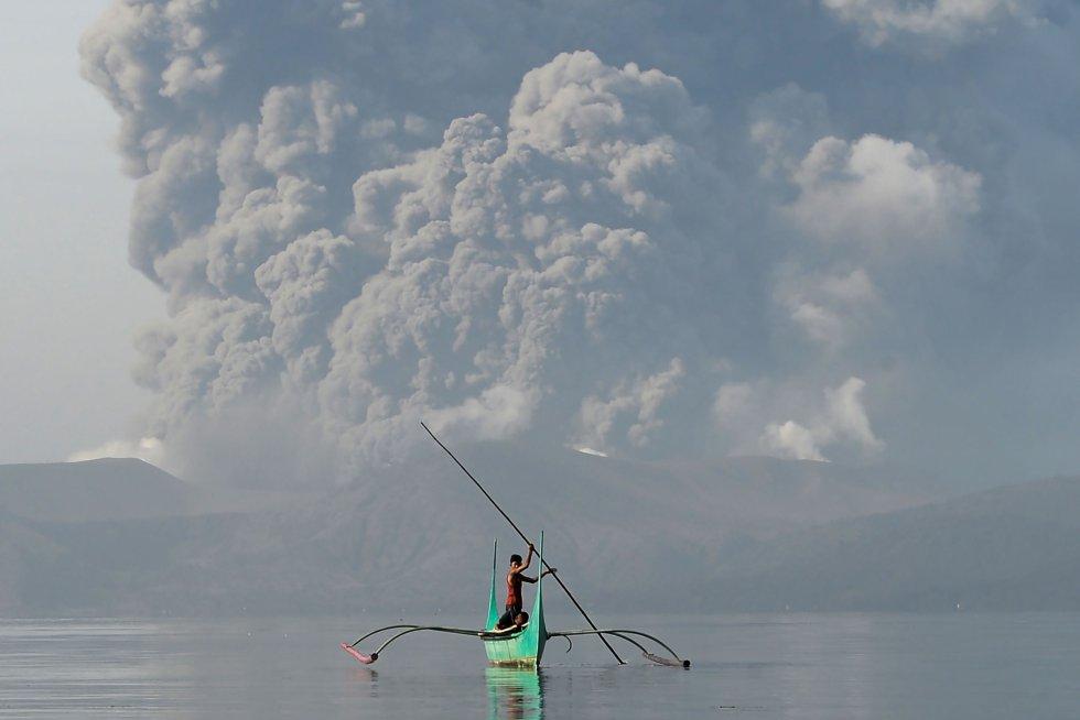Un joven que vive al pie del volcán Taal monta una canoa mientras el volcán arroja cenizas como se ve desde la ciudad de Tanauan, al sur de Manila, el 13 de enero.