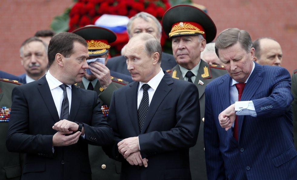 En la imagen, el presidente ruso y el primer ministro, junto al jefe de gabinete de la Administración Presidencial, Sergei Ivanov (a la derecha), asisten a una ceremonia de colocación de coronas en la Tumba del Soldado Desconocido en los muros del Kremlin en Moscú, el 22 de junio de 2013.