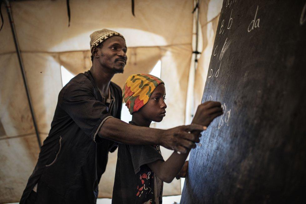 El profesor Omar Cissé corrige la escritura de un niño en una escuela montada por Unicef en Mopti para los desplazados del conflicto que vive Malí desde hace ocho años.