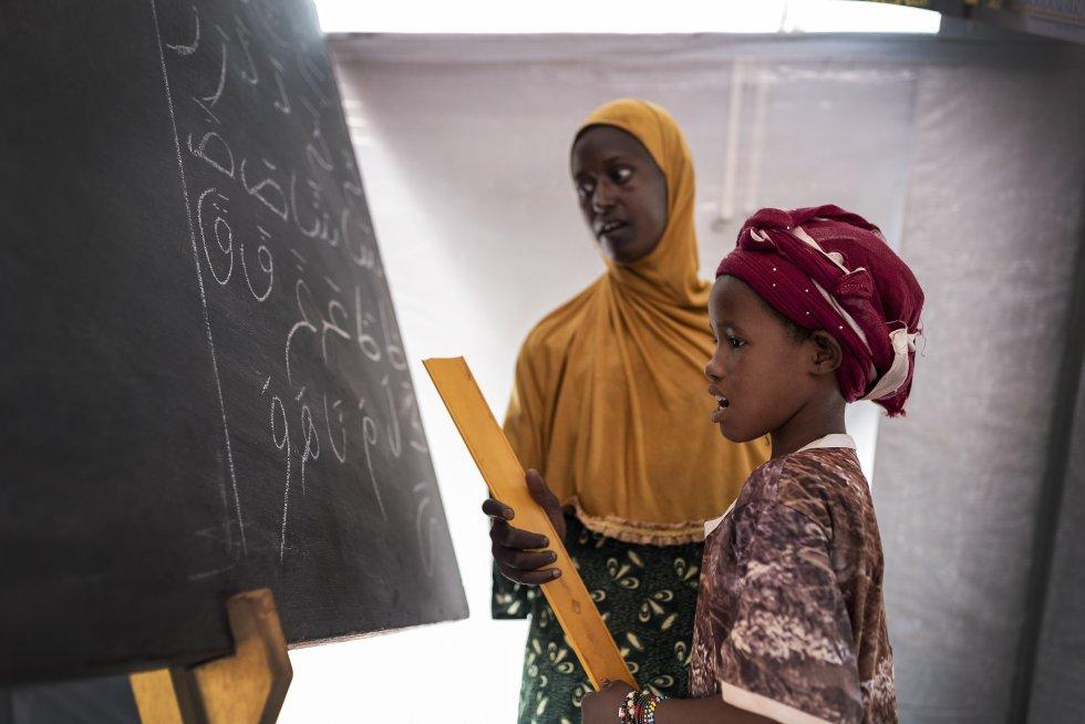 Una niña aprende a leer en árabe en un aula para desplazados montada por Unicef en el terreno de fútbol de Mopti.