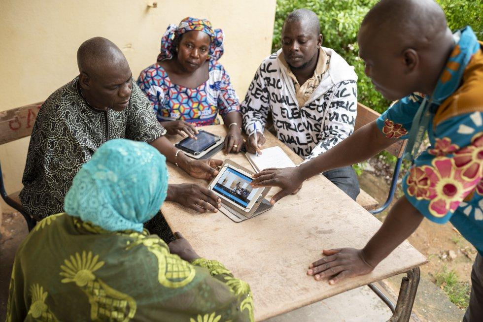 Mahamadou Hassaye Maïga, director de la escuela Banguetabá B, sujeta una tablet y muestra a cuatro profesores del centro el método pedagógico para trabajar con grandes grupos.