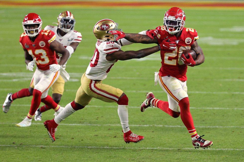 Damien Williams (número 26) de los Chiefs bloquea a uno de sus rivales con uno de sus brazos.