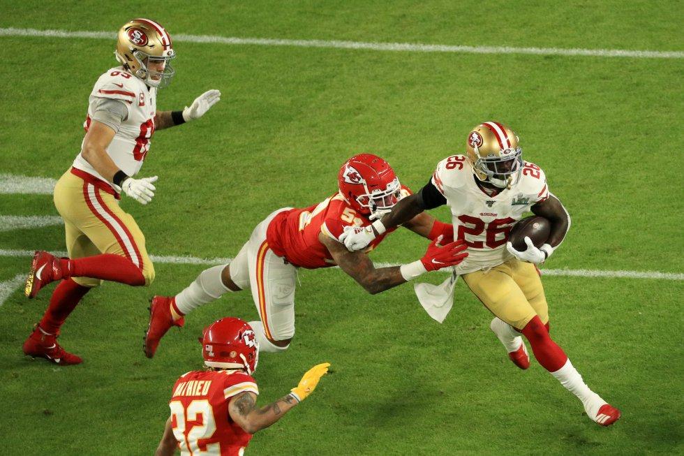 Tevin Coleman (número 26) de los 49ers lleva el balón contra Damien Wilson (54) de los Kansas City Chiefs en el primer cuarto del partido.