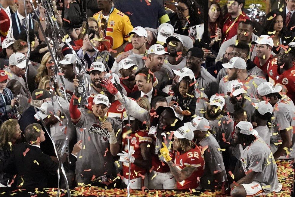 Patrick Mahomes sostiene el trofeo rodeado de su equipo tras haber ganado la Super Bowl.