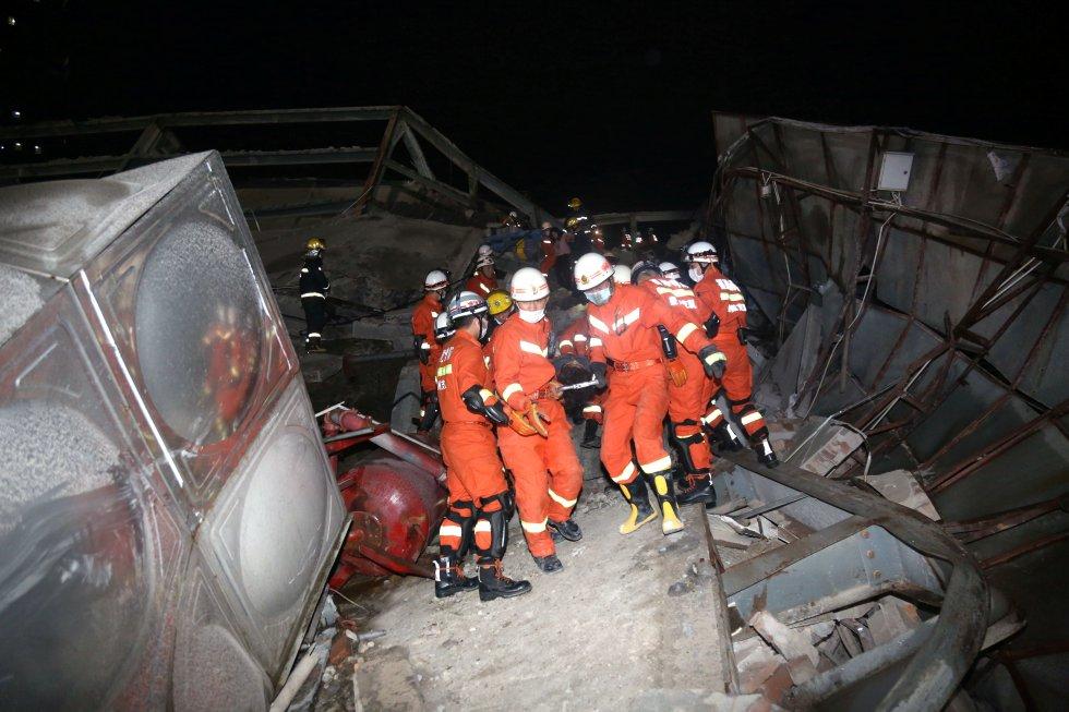 Las autoridades chinas mandaron 150 trabajadores para las tareas de rescate en el hotel derrumbado. En la imagen, los bomberos sacan a una de las víctimas de los escombros.