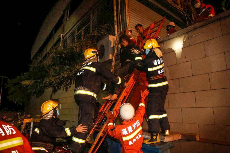 Una mujer baja por una escalera, ayudada por los bomberos, tras el derrumbe del edificio que albergaba al hotel derrumbado.