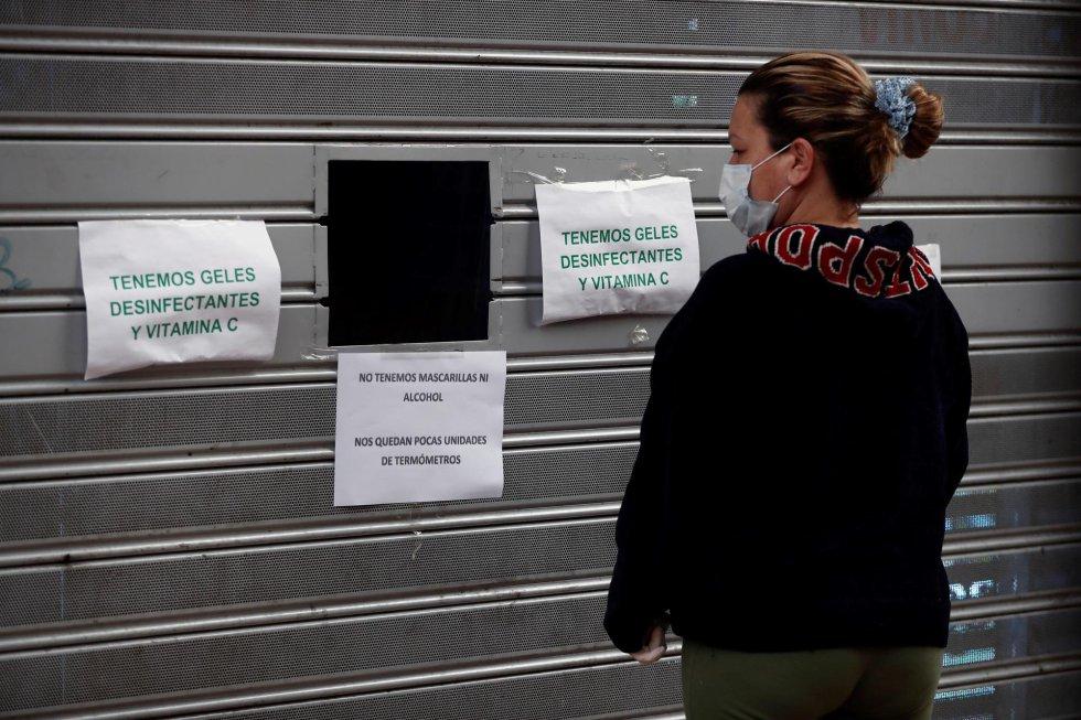 Una mujer lee los carteles pegados en el cierre de un negocio este martes, vigésima cuarta jornada desde que se decretase el estado de alarma para frenar la epidemia del coronavirus.