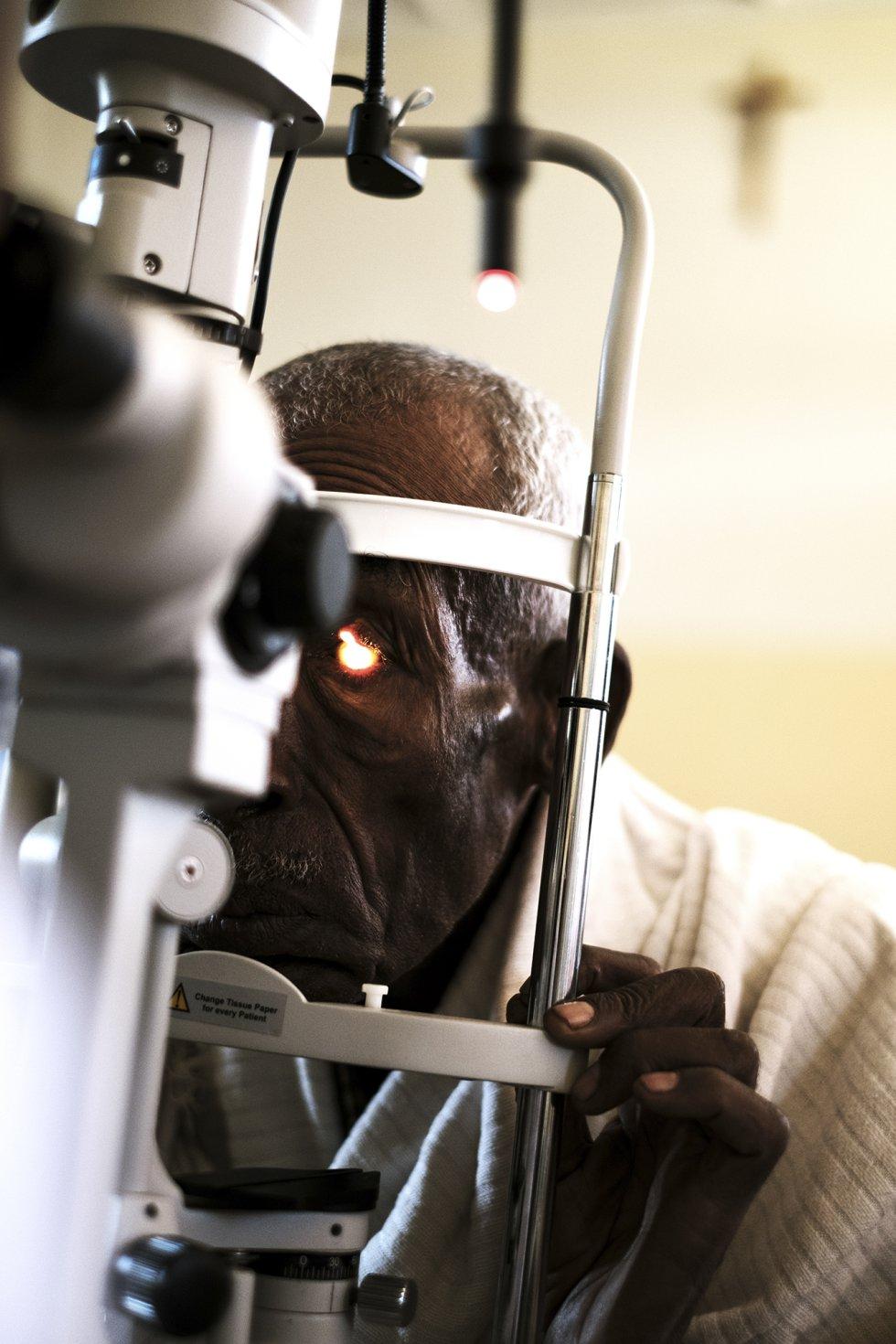 En el centro de Salud de Wassserà trabaja un equipo de oftalmólogos de la organización italiana Amoa Onlus. Los pocos centros de salud como este, en Wasserà, son los únicos lugares adonde la población local, en su mayoría pequeños agricultores, que viven en chozas sin acceso a agua potable y electricidad, puede acudir a revisarse la vista. En la imagen, un anciano durante un examen oftalmológico con lámpara de hendidura.