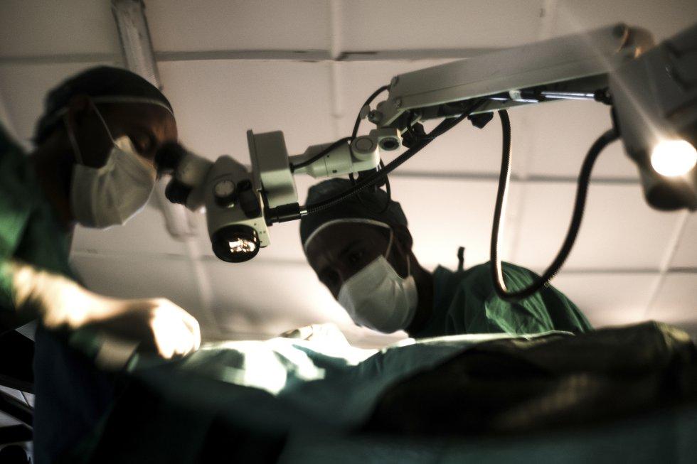 El doctor Zelalem y su asistente durante una operación de cataratas en el Centro de Salud de Wasserà. Zelalem opera un día cada dos meses en el Centro de Salud, adonde deben trasladarse los pacientes de las aldeas vecinas para la intervención. Es uno de los aproximadamente 130 oftalmólogos que trabajan en Etiopía, con una población de más de 114 millones de personas.
