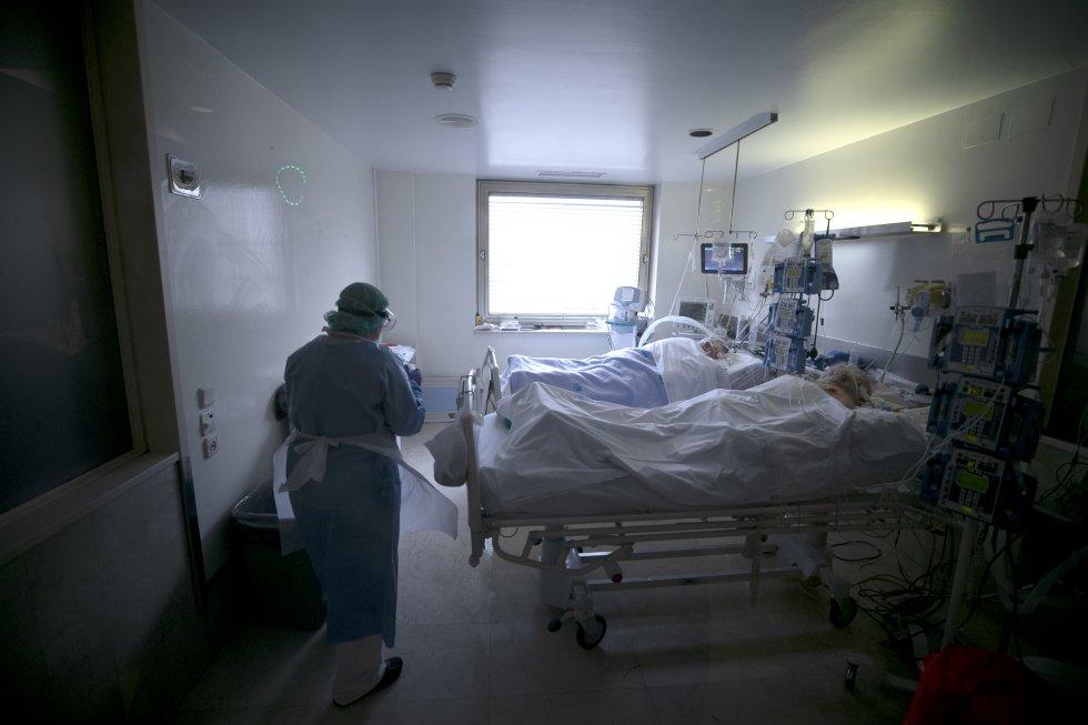 Una empleada de limpieza en una de las habitaciones de una UCI en la que hay dos pacientes entubados afectados por covid-19.