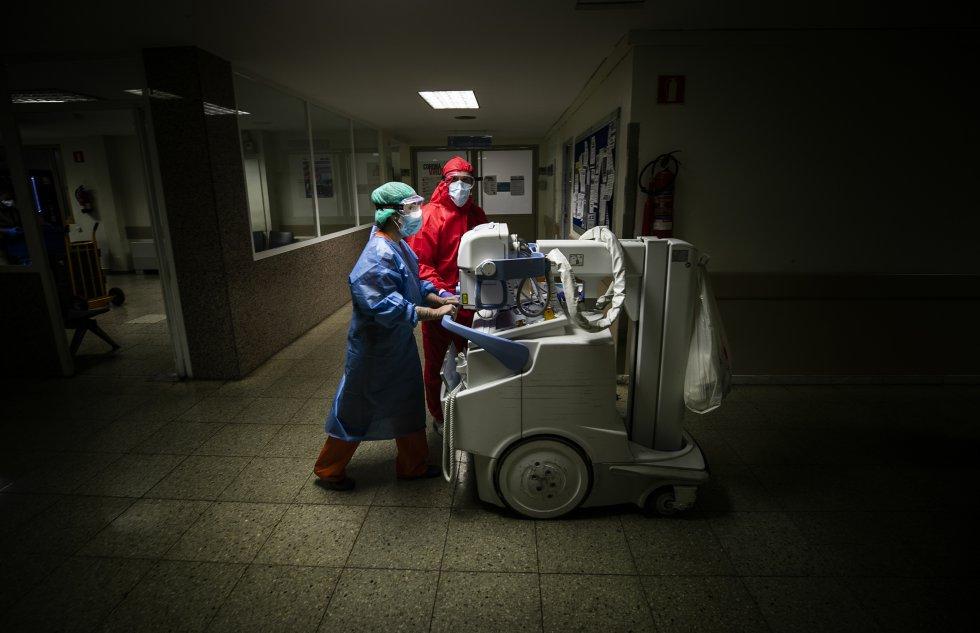 Dos sanitarios trasladan un equipo portátil de radiología por una de las plantas destinadas a UCI del hospital. Los equipos de rediodiagnóstico son fundamentales para el tratamiento de la enfermedad ya que permiten evaluar el daño pulmonar en pacientesgraves, que no pueden ser trasladados fuera de la unidad de intensivos.