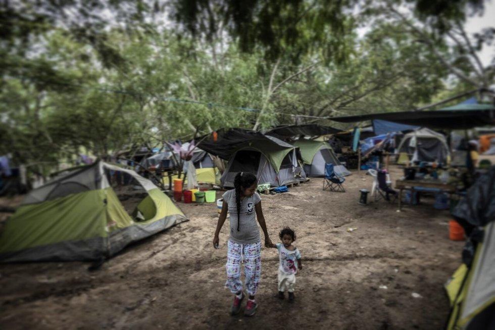 Lucía, una joven madre del Estado mexicano de Guerrero, camina con su pequeña hija por un campamento improvisado de migrantes en Matamoros, en el Estado de Tamaulipas, al norte de México.