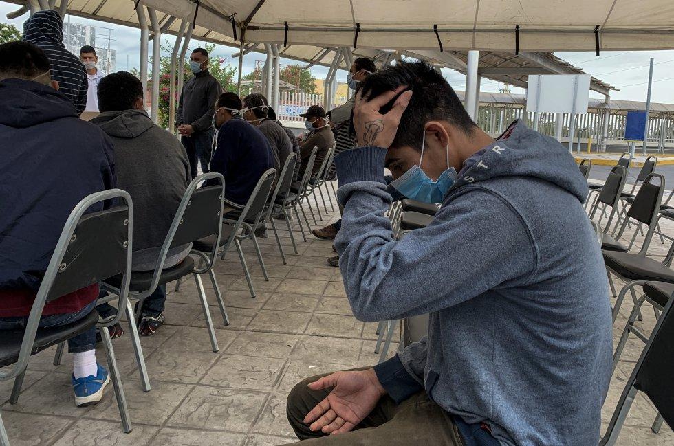 Sentado y con la cara cubierta con un tapabocas, un hombre que fue detenido cuando intentaba cruzar la frontera escucha sus derechos en un centro de migración en Tamaulipas.