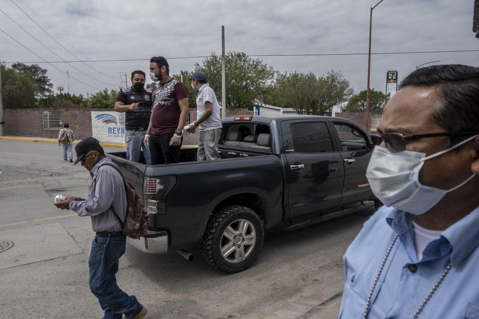 Voluntarios reparten comida desde un vehículo a los migrantes y deportados que permanecen varados a las afueras de un refugio en la frontera. Ante la emergencia por el coronavirus, muchos de estos albergues han tenido que cerrar y permanecer en cuarentena.