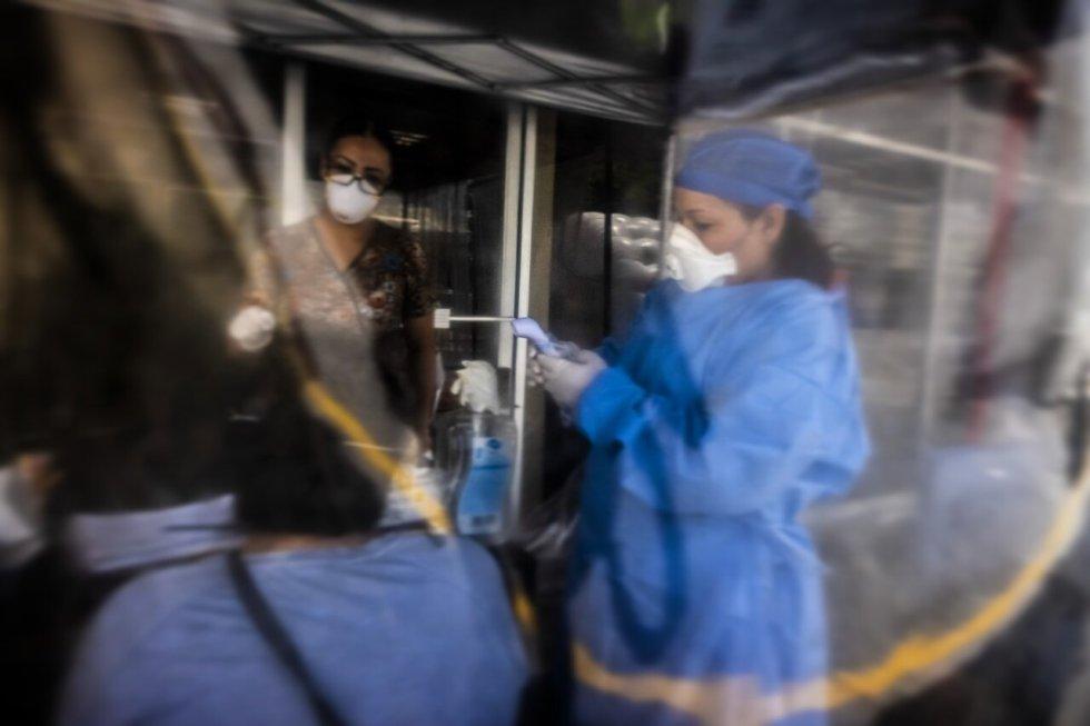 Personal médico toma la temperatura a una paciente en un puesto de control de emergencia instalado en Nuevo Laredo, Tamaulipas.