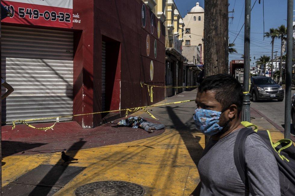 El cuerpo de una mujer no identificada yace sobre la acera de una calle en pleno centro de Tijuana. El cadáver permaneció más de 12 horas en el lugar sin ser removido por las autoridades, debido a la sobrecarga de trabajo de los servicios forenses en la entidad.