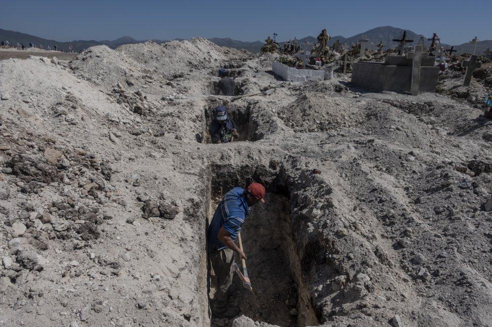Trabajadores de un panteón municipal excavan más tumbas en un área nueva del cementerio para recibir a los muertos de la epidemia.