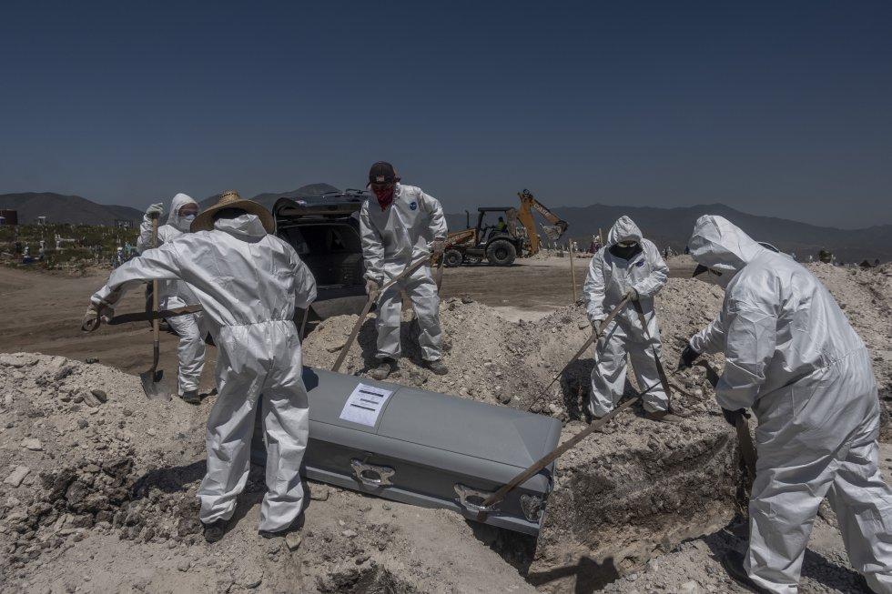 Sepultureros entierran el cadáver de una víctima de covid-19. Además de arrojar agua con cloro al féretro, utilizan unas cintas para no tocarlo.