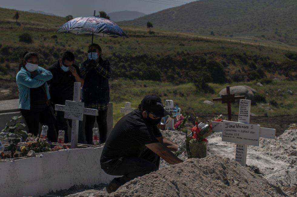 Los trabajadores del cementerio permiten el paso de los familiares de la víctima para poder dejar sus ofrendas florales únicamente después de que el ataúd quede bajo tierra.