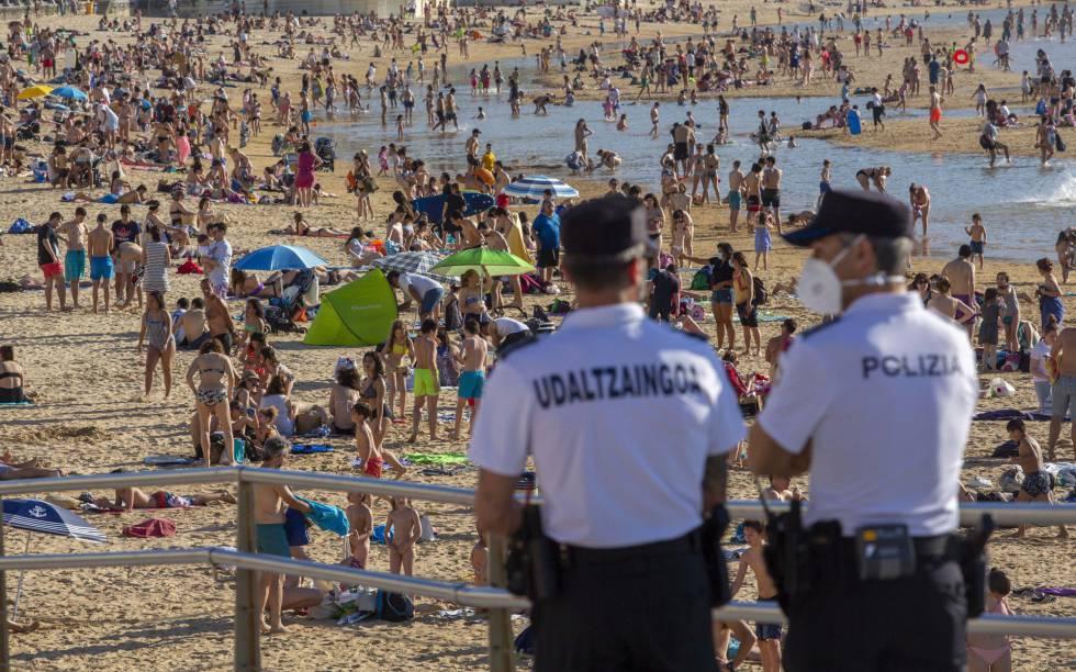 Dos agentes de policía de San Sebastián controlan el acceso a la playa de La Concha.