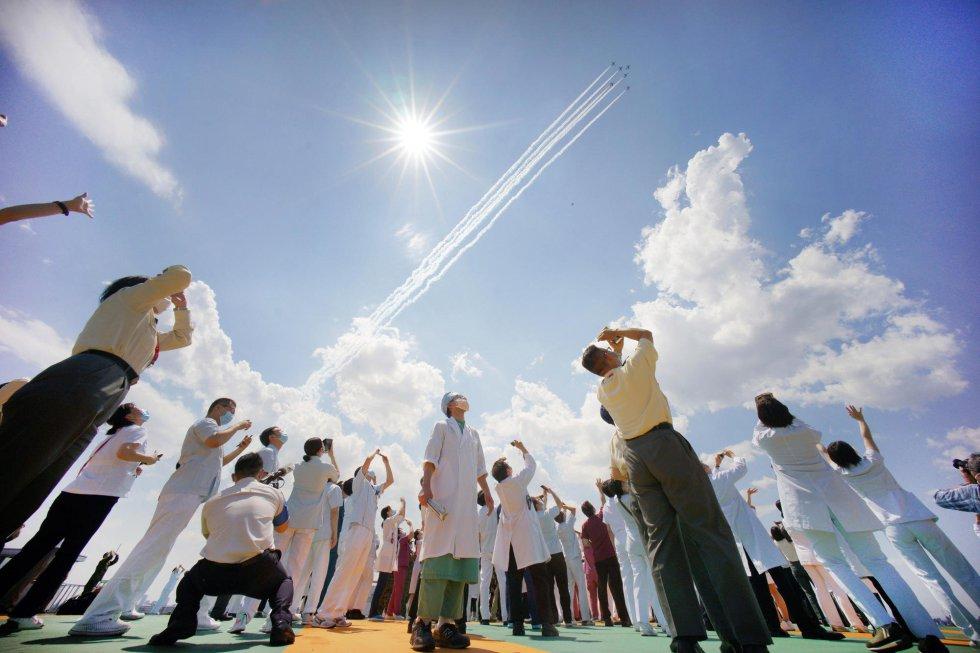 Personal sanitario del Hospital Central de Tokio observa el paso del escuadrón de demostración acrobático 'Impulso Azul'.