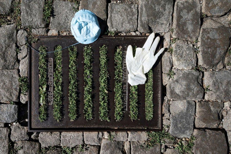 Un guante de plástico y una masacarilla junto a un sumidero taponado por la hierba en una calle adoquinada de Ávila.