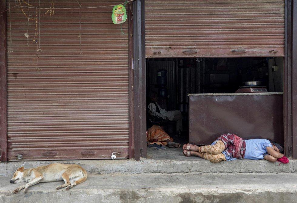 Un jornalero duerme una siesta durante sexagesimoséptima jornada del confinamiento impuesto para frenar la pandemia del coronavirus en Katmandú, Nepal.