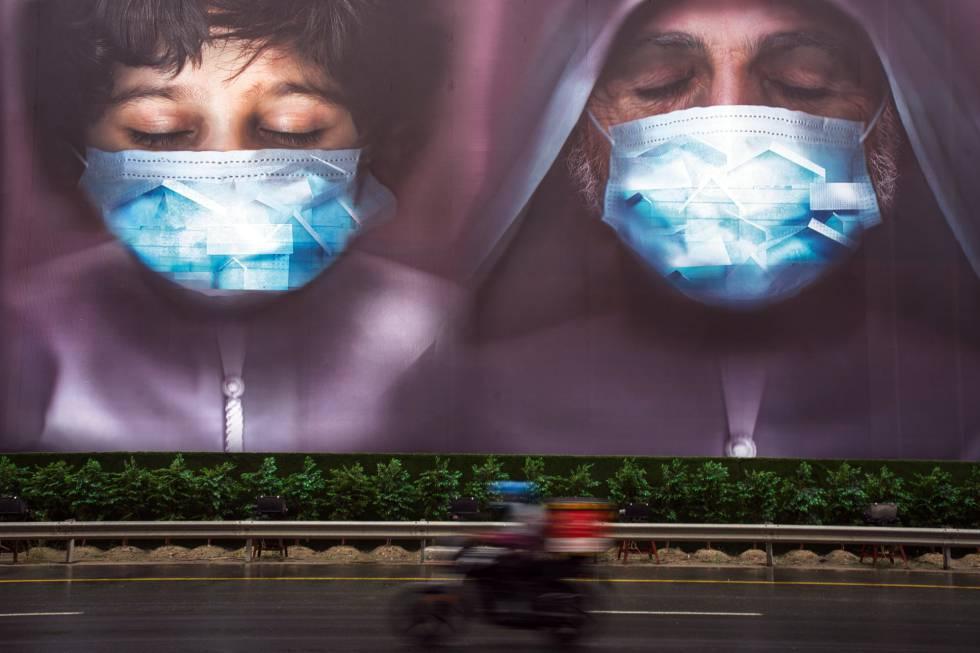 Un repartidor pasa junto a una valla publicitaria instando a las personas a utilizar mascarillas en Dubái (Emiratos Árabes).