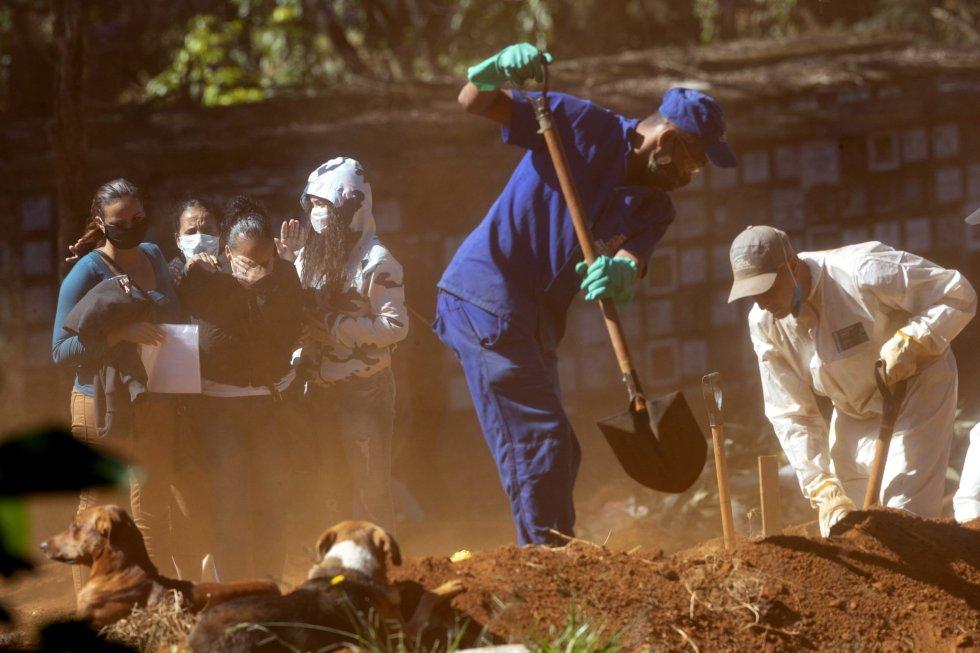 Dos sepultureros echan tierra sobre el ataúd de una víctima de coronavirus mientras sus familiares lloran su pérdida, en un cementerio de Vila Formosa de São Paulo (Brasil).
