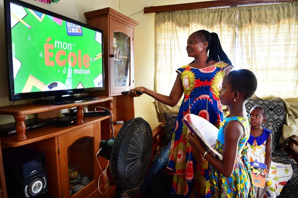 """La madre de Ange, de ocho años, ayuda a sintonizar su televisión para acceder a las clases desde casa, en Man, al oeste de Costa de Marfil. """"Me gusta estudiar en casa. Mi madre es maestra y me ayuda mucho. Por supuesto que extraño a mis amigos, pero puedo dormir un poco más por la mañana. Cuando sea mayor quiero ser abogada o jueza"""", dice la niña. En este país africano, desde que comenzó la pandemia, Unicef ha estado trabajando con el Ministerio de Educación en una iniciativa llamada 'Escuela en casa' que incluye la grabación de lecciones que se transmiten en la televisión y radio nacionales."""