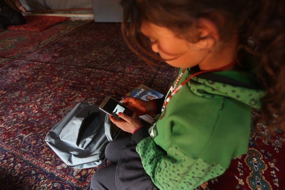 """En Siria, millones de niños en edad escolar han visto interrumpida su educación debido a la suspensión de actividades como medida de precaución contra la propagación de la covid-19. Sin embargo, los maestros y los niños han encontrado formas de mitigar el impacto de esta suspensión y continuar su educación. """"Los profesores aquí crearon grupos de WhatsApp para conectarnos con nuestros estudiantes. Con la ayuda de sus padres, pueden seguir las lecciones e incluso enviarnos preguntas"""". Una de las personas que se benefician de estas clases remotas es María, de nueve años, que nació en un pueblo cerca de Maarat Al-Numan, y ella y su familia buscaron seguridad más al norte en el campamento de Kili, donde también se unió a la escuela del campamento. """"Estas lecciones pregrabadas no son un sustituto del aula"""", dice Walid, maestro en las carpas educativas apoyadas por Unicef en el campamento de desplazados internos en Kili, a 20 kilómetros al norte de Idlib, """"pero hasta que podamos dar la bienvenida a nuestros estudiantes nuevamente en sus aulas, esta es la mejor alternativa que tenemos por ahora""""."""