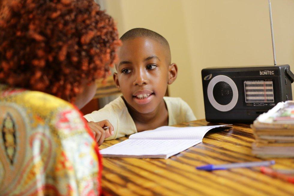La radio es la tercera plataforma más utilizada por los gobiernos para ofrecer educación mientras las escuelas permanecen cerradas: un 60% de los 127 países, según recoge un estudio de Unicef. Irasubiza Uwayo Merveille, de 10 años, hace sus deberes junto a su madre, Nyiraneza Jeannette, después de escuchar juntas la lección de radio de Merveille Primary 3. La escuela de Merveille está actualmente cerrada para ayudar a prevenir la propagación de la covid-19.