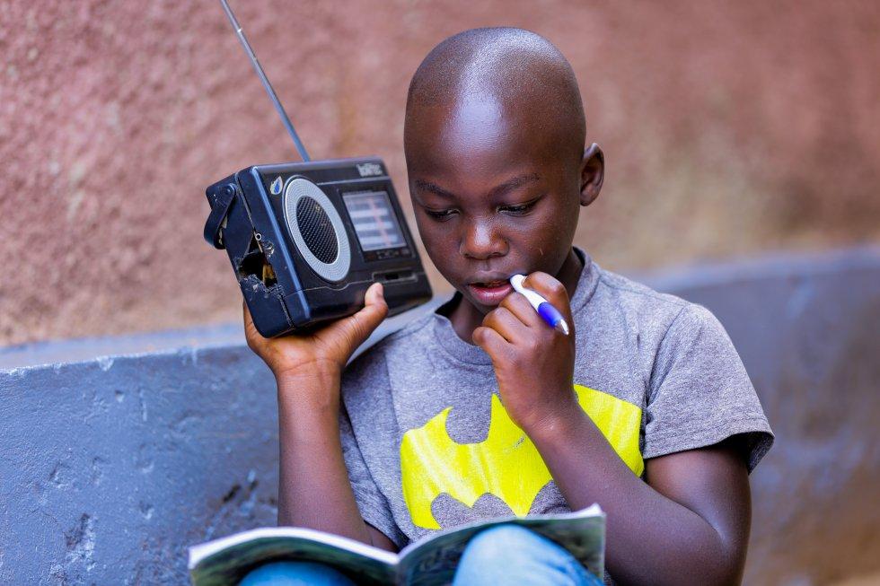 """Igihozo Kevin, de 11 años, estudia en casa escuchando sus lecciones en una radio. """"Es el medio más popular y accesible en Ruanda. Como emisora pública nacional, las estaciones de Rwanda Broadcasting Agency llegan a casi el 99% de la población, incluidas Radio Rwanda y cinco emisoras regionales"""", explica Aldo Havugimana, director de Radio de Rwanda Broadcasting Agency. """"Dado este alcance expansivo, las lecciones por este medio se identificaron como la solución inmediata más adecuada""""."""