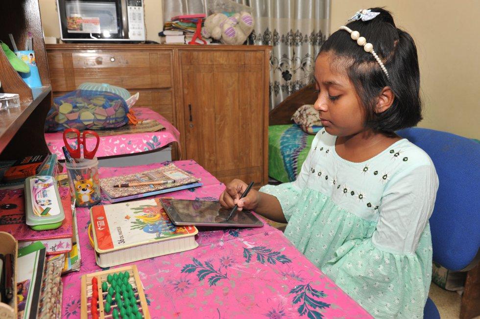 Mounee Mahdeya, de 10 años, usa su tablet para completar sus deberes en su casa en Dacca, la capital de Bangladés. Su escuela ha introducido el aprendizaje a distancia a través de plataformas digitales para continuar la educación de los niños durante el bloqueo indefinido impuesto en todo el país por la pandemia.