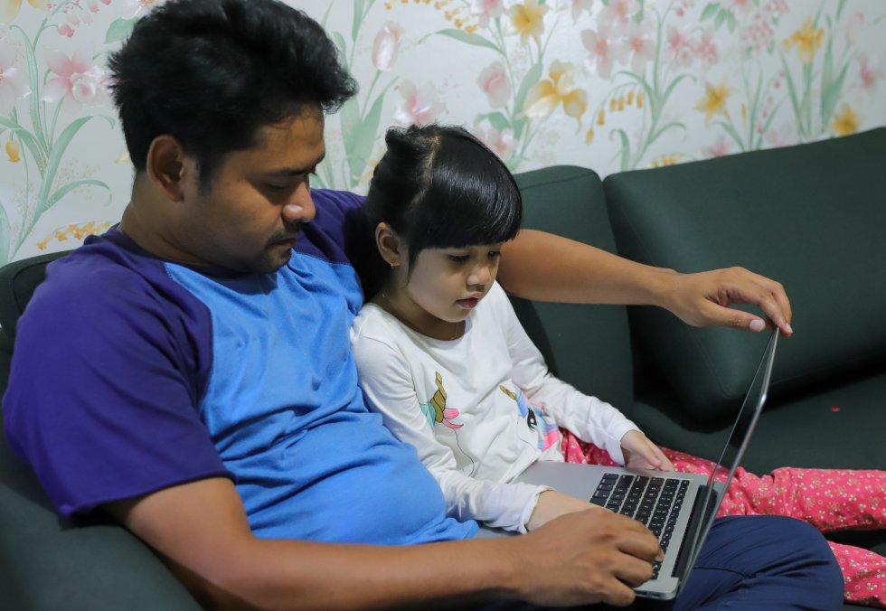 """Kimy, de seis años, estudia en casa con la ayuda de su padre en Yakarta, la capital de Indonesia. Ella y su hermana Feli, de cinco años, han estado aprendiendo a distancia desde la segunda semana de marzo, cuando el Gobierno cerró todas las aulas. Kimy y Feli están en el jardín de infancia y su maestra les envía una tarea todos los días que su padre les ayuda a completar. """"Me gusta estudiar en casa, pero extraño a mis amigos en la escuela"""", dice Kimy. Unicef está apoyando al Ministerio de Educación y Cultura para que transmita un programa educativo de televisión para ayudar a los escolares con acceso limitado a internet a aprender desde casa."""