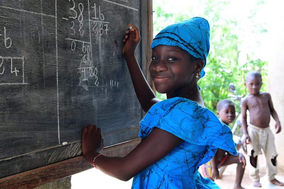 """Fatimata Bagayogo, de 11 años, estudia en su casa durante la crisis de la pandemia, en Odienné, al norte de Costa de Marfil. Como las escuelas están cerradas, ella asiste a clases por televisión y practica matemáticas en una pizarra que le ha comprado su padre. Sidiki Bagayogo, de 47 años, es profesor y conoce la importancia de la educación. """"Me gusta que mi padre me ayude. No me obliga. Me gusta estudiar y extraño la escuela. Echo de menos a mis amigos, pero ahora ayudo a mi madre a cocinar cuando estoy aburrida. Quiero ser médica"""", dice la pequeña."""