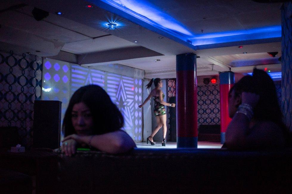 Varias mujeres y niñas permanecen sentadas mientras otra baila para los clientes en un bar con espectáculo de los muchos que sirven de tapadera a un burdel en el centro de Katmandú, Nepal. rnrn A menudo, la promesa de un empleo en las mayores ciudades nepalíes tienta a las chicas pobres, ingenuas, y muchas veces maltratadas, para que caigan en el trabajo forzado y la explotación sexual en bares con espectáculos de baile y salones de masaje para una clientela extranjera en su mayoría. rnrn Mientras que en el sector del espectáculo es frecuente intentar evitar la prostitución, los bares de bailarinas, los salones de masajes y los restaurantes con reservados son lugares de paso obligado para quienes buscan sexo. Las trabajadoras están prácticamente desprotegidas frente al acoso, y muchas veces los gerentes del local acaban obligándolas a prostituirse. En estos establecimientos, los traficantes también pueden tentar a las chicas para que crucen la frontera con India con la promesa de obtener un trabajo mejor. Una vez allí, es probable que acaben obligadas a ejercer la prostitución en vez de disfrutando la oportunidad en el negocio del espectáculo que les volvieron a prometer.