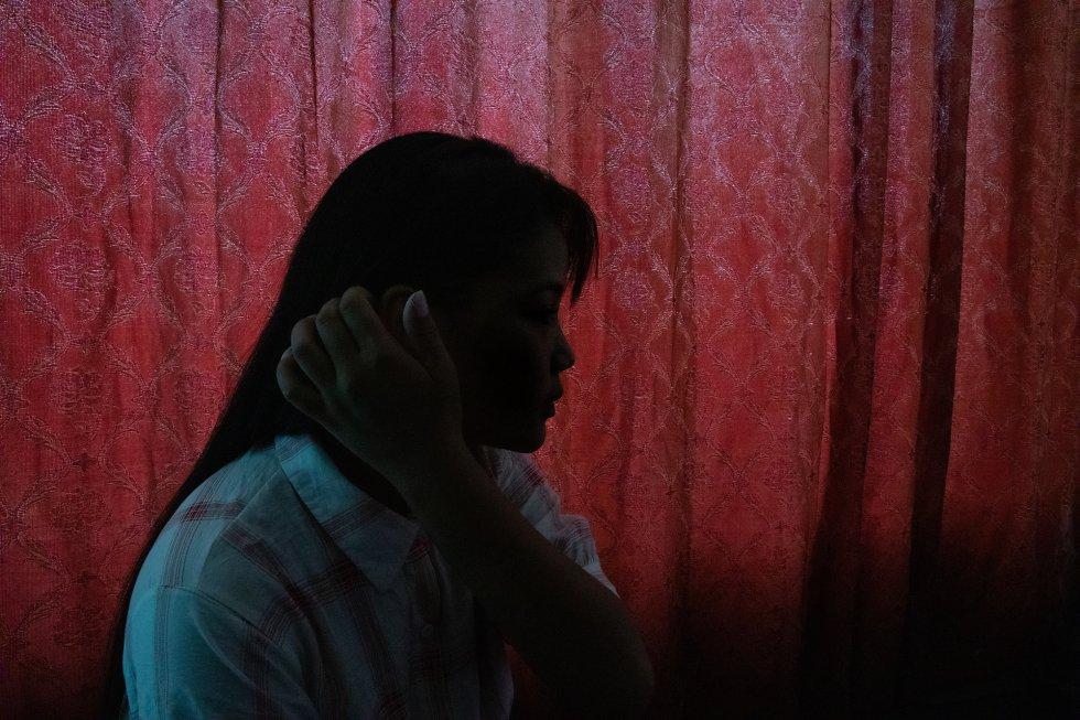 """E., de 20 años, posa en la residencia temporal de la ONG contra el tráfico de personas 3 Angels Nepal, donde vive después de que los vigilantes de la organización la rescatasen cuando intentaba cruzar la frontera por la ciudad nepalí de Bhairahawa para reunirse con un posible traficante que le había prometido un trabajo en India. Las redes sociales permiten a los traficantes tentar y captar con más facilidad a sus víctimas, y convencerlas para que ellas mismas vayan ingenuamente a su encuentro en las grandes ciudades de Nepal o al otro lado de la frontera con India sin el riesgo de que ser descubiertos y detenidos. Además, han multiplicado sus posibilidades al permitirles tentar a distancia a varias posibles víctimas al mismo tiempo. Según 3 Angels Nepal, cada día más de 54 mujeres y niñas son trasladadas ilegalmente de Nepal a India. Un informe de 2019 de la Comisión de Derechos Humanos de Nepal afirma que """"cada año se rescata de India a casi 1.000 mujeres y niñas nepalíes que han sido trasladadas al país vecino para destinarlas a la prostitución, el trabajo forzado o el servicio doméstico, o como parada intermedia antes de llevarlas a terceros países"""". Algunas mujeres y niñas son captadas o tentadas con la promesa de trabajar o estudiar en India o en otros países del extranjero. Sin embargo, una vez allí son explotadas y maltratadas físicamente en condiciones rayanas en la esclavitud, o acaban obligadas a prostituirse."""