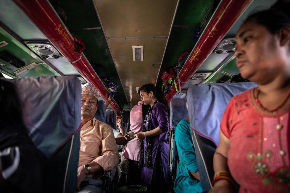 """Tras ordenar a un autobús de pasajeros que se dirigía a India que se detuviese en la ciudad fronteriza nepalí de Bhairahawa, Maheshwori Nepali (centro), antigua víctima del tráfico de personas convertida en colaboradora de una ONG antitrata, interroga a una pareja (no aparece en la imagen) y comprueba sus documentos para intentar determinar si realmente están emparentados o si se trata de un traficante que viaja con su víctima, ajena a lo que le espera. Las ONG nepalíes contra el tráfico de personas, como 3 Angels, para la que trabaja Maheshwori tras haber sido rescatada por ella, sitúan pequeños puestos de control a lo largo de la frontera con India para interceptar casos. Según la organización, los establecimientos que tiene distribuidos a lo largo de los 1.758 kilómetros de frontera impiden cada día el paso de una media de 12 niñas víctimas del tráfico. 3 Angels sostiene que esta es la forma de rescate más eficaz. Según la policía nepalí, citada por el Kathmandu Post, """"el año pasado, 2.104 ciudadanos nepalís posibles víctimas del tráfico de personas fueron devueltos desde la frontera India-Nepal, y las cifras de varias ONG muestran que, a raíz del control de varios pasos fronterizos, se rescató a más de 10.000 en el mismo periodo de tiempo"""". No obstante, en medio del colosal flujo de personas, es difícil determinar si los motivos para cruzar la frontera que declaran las personas son verdaderos, especialmente cuando los traficantes -que se hacen pasar por parejas, parientes o agentes de contratación, entre otras estratagemas- aleccionan a sus víctimas para que mientan cuando los vigilantes de la frontera las detienen mientras viajan solas o en compañía de sus captores creyendo que, al otro lado de la frontera, les darán la oportunidad de tener una vida mejor."""